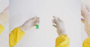 防護服とゴム手袋で完全防備で試験管の検体を検査する研究員の手